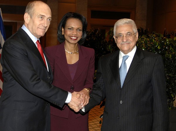 Former Israeli Prime Minister Ehud Olmert and Palestinean President Mahumoud Abbas  shake hands at an American photoshoot.